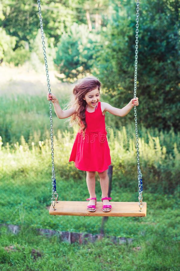 Piękna mała dziewczynka jest sianding i uśmiechnięta na huśtawce przy summe zdjęcia royalty free