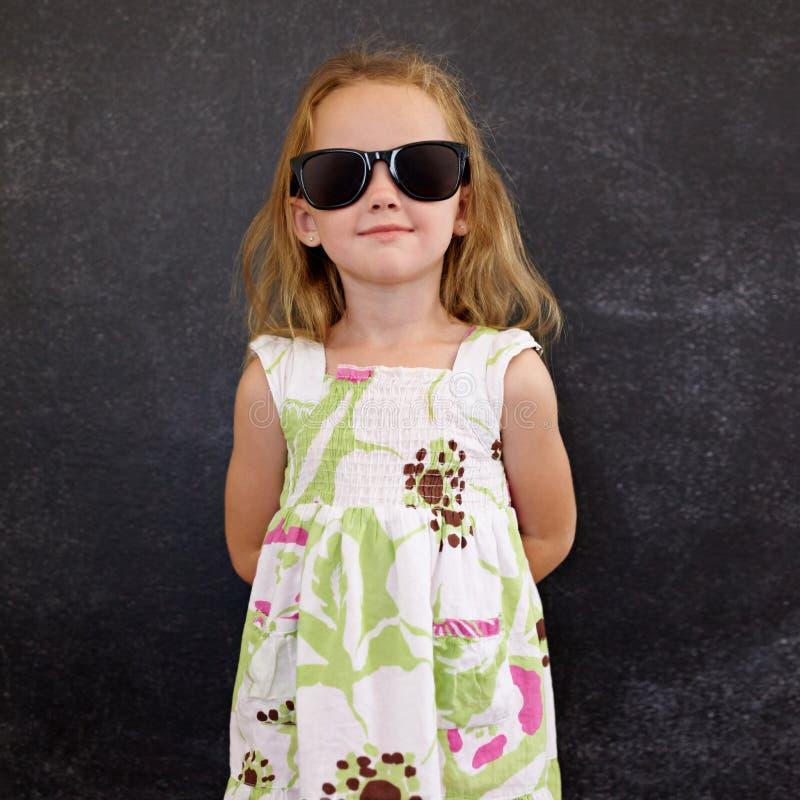 Piękna mała dziewczynka jest ubranym okulary przeciwsłonecznych fotografia royalty free