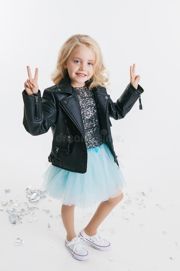 Piękna mała dziewczynka jest usytuowanym na wakacyjnym przyjęciu w sukni z cekinami i czarną kurtką z kędzierzawą blondynki fryzu fotografia royalty free
