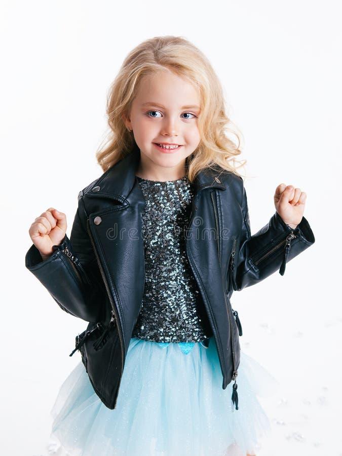 Piękna mała dziewczynka jest usytuowanym na wakacyjnym przyjęciu w sukni z cekinami i czarną kurtką z kędzierzawą blondynki fryzu obraz stock