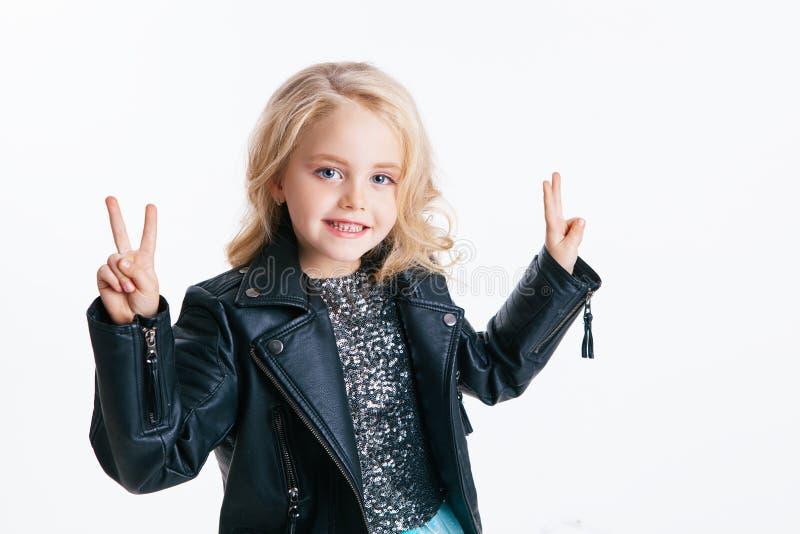 Piękna mała dziewczynka jest usytuowanym na wakacyjnym przyjęciu w sukni z cekinami i czarną kurtką z kędzierzawą blondynki fryzu zdjęcie stock