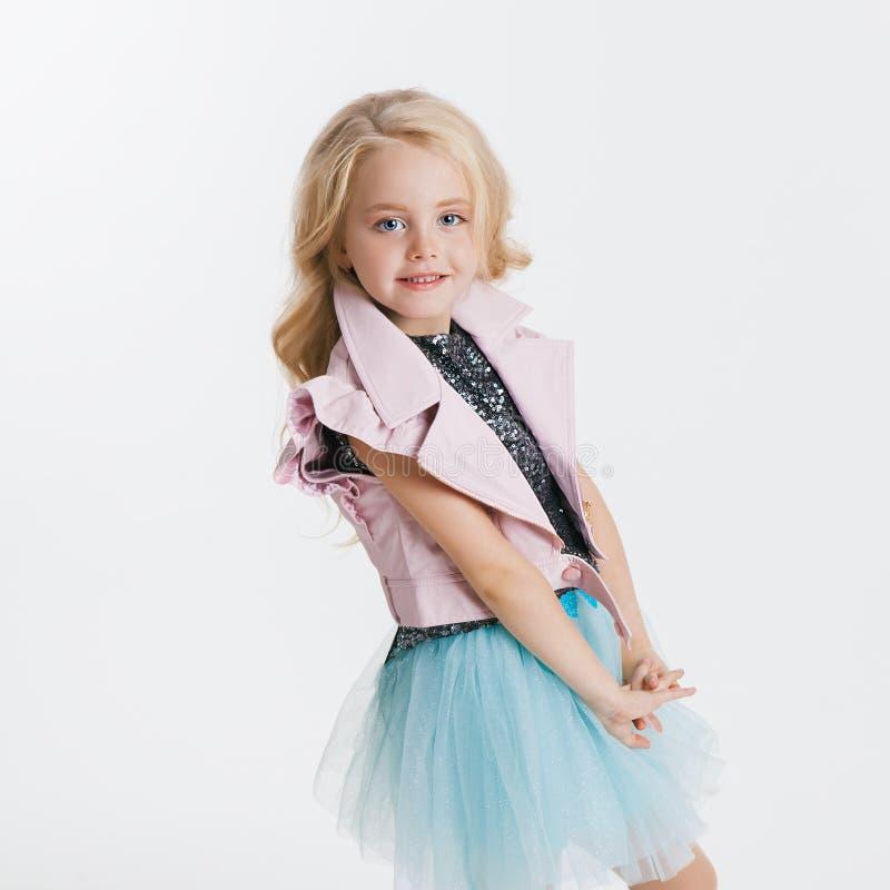 Piękna mała dziewczynka jest usytuowanym na wakacyjnym przyjęciu w sukni z cekinami i różową kurtką z kędzierzawą blondynki fryzu obrazy royalty free