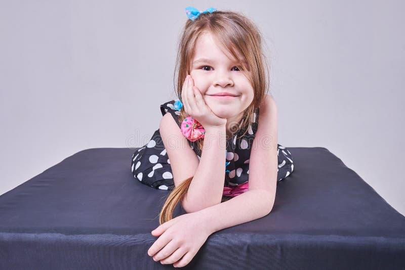 Piękna mała dziewczynka kłama, trzymający jej głowę z jej rękami i uśmiechami, zdjęcia royalty free