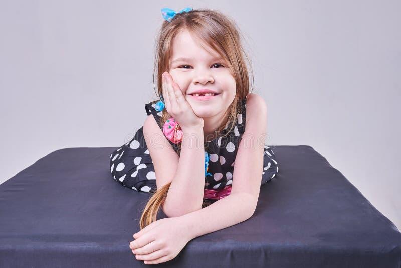 Piękna mała dziewczynka kłama, trzymający jej głowę z jej rękami i uśmiechami, zdjęcie stock
