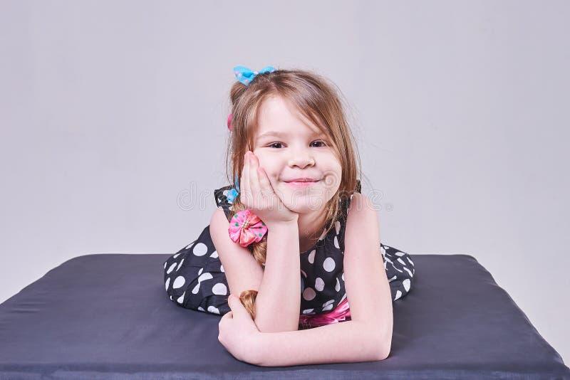 Piękna mała dziewczynka kłama, trzymający jej głowę z jej rękami i uśmiechami, zdjęcie royalty free
