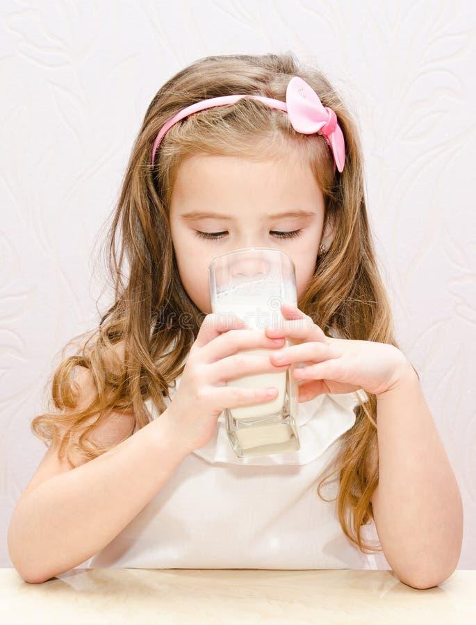 Piękna mała dziewczynka pije mleko zdjęcie royalty free