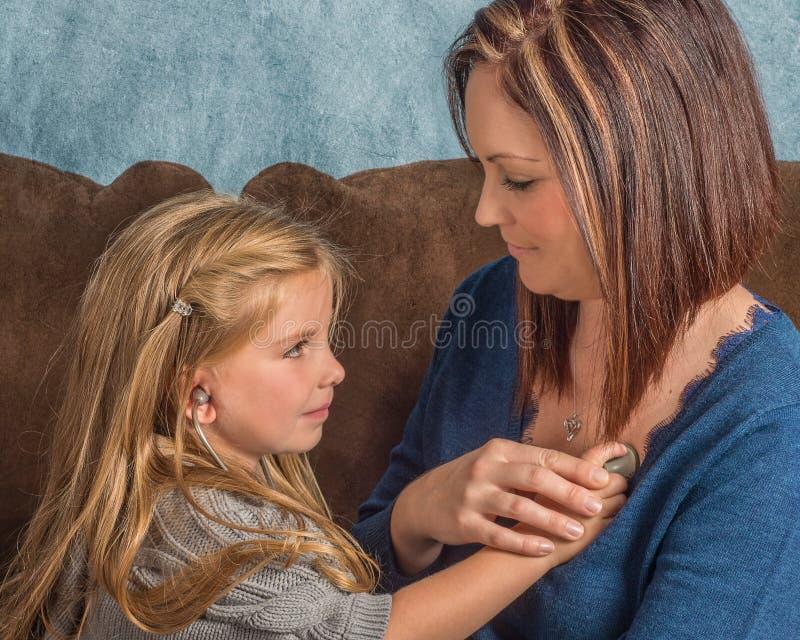 Piękna mała dziewczynka słucha jej mamy kierowe z stethos zdjęcia stock