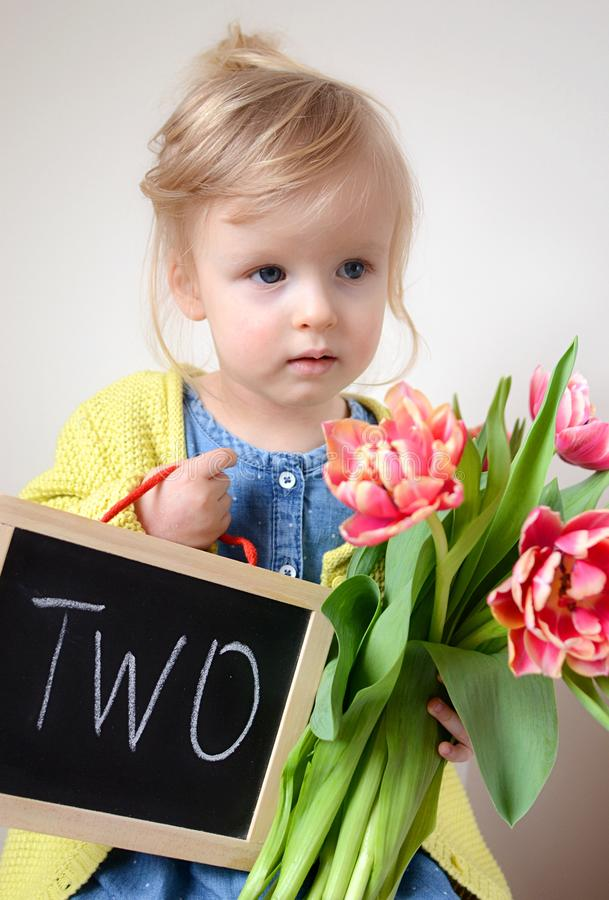 Piękna mała dziewczynka trzyma bukiet czerwoni tulipany fotografia stock