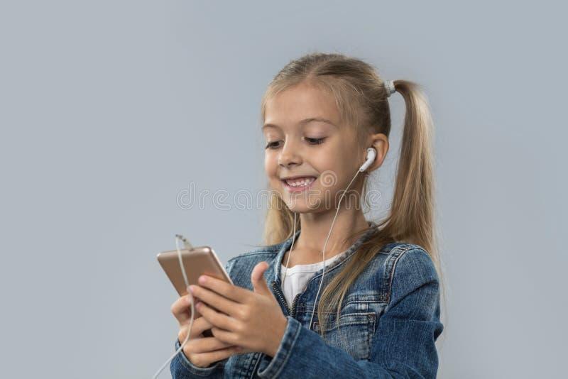 Piękna mała dziewczynka Używa komórka Mądrze telefon Słucha Muzycznych odzieży słuchawek Szczęśliwy ono Uśmiecha się Odizolowywam fotografia royalty free