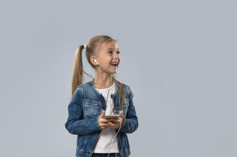 Piękna mała dziewczynka Używa Mądrze telefon Słucha Muzycznych odzieży słuchawek Szczęśliwego Uśmiechniętego spojrzenie Kopiować  zdjęcia stock