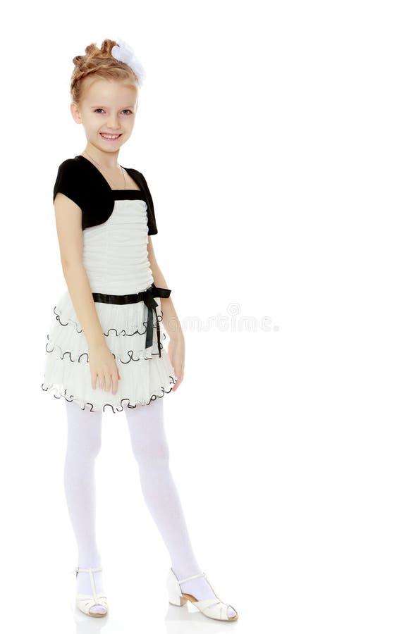 Piękna mała dziewczynka w białej krótkiej sukni z czarnym paskiem zdjęcia royalty free