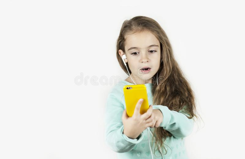 Piękna mała dziewczynka w hełmofonach z telefonem w ona ręki emocjonalnie raduje się na odosobnionym tle i opowiada obrazy stock