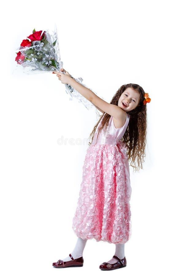 Piękna mała dziewczynka w różowej sukni z bukietem czerwone róże obraz stock