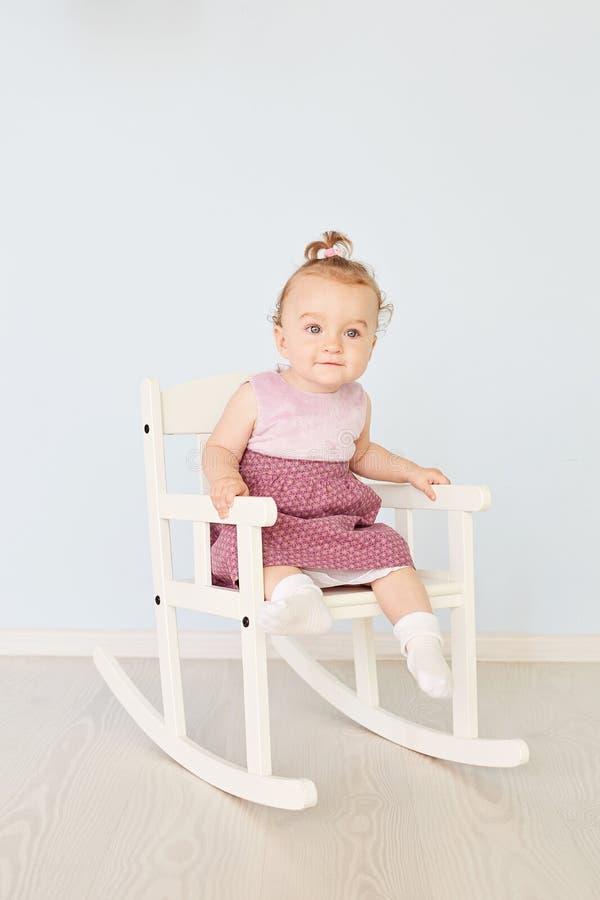 Piękna mała dziewczynka w sukni siedzi na białym krześle obrazy stock