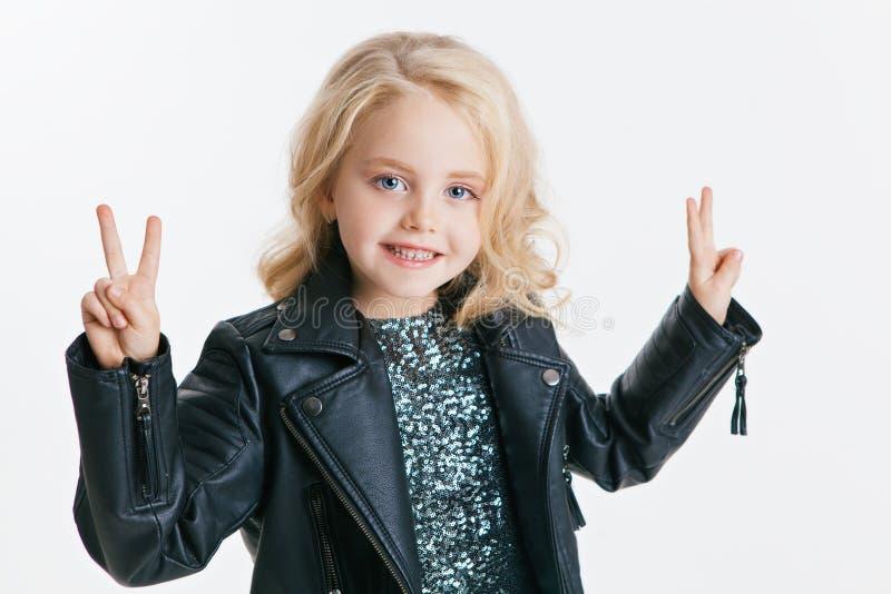 Piękna mała dziewczynka z kędzierzawą blondynki fryzurą na wakacyjnym przyjęciu w sukni z cekinami i czarną kurtką srebro zdjęcie stock