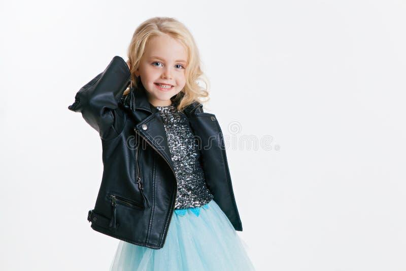 Piękna mała dziewczynka z kędzierzawą blondynki fryzurą na wakacyjnym przyjęciu w sukni z cekinami i czarną kurtką srebro obraz stock