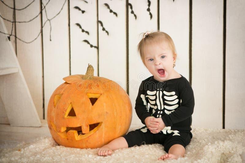 Piękna mała dziewczynka z puszka syndromu obsiadaniem blisko bani na Halloween ubierał jako kościec obrazy stock