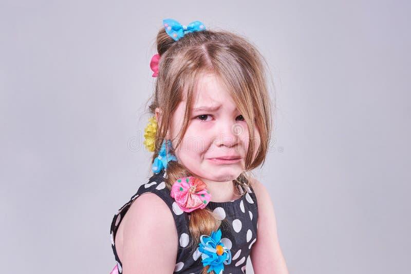 Piękna mała dziewczynka z smutnym wyrażeniem i łzami w jej oczach, obrazy royalty free