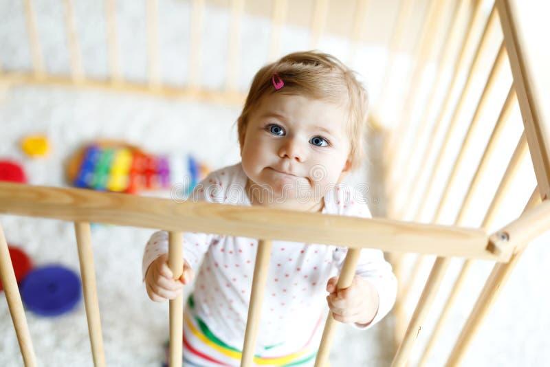 Piękna mała dziewczynki pozycja wśrodku kojec Śliczny uroczy dziecko bawić się z kolorową zabawką zdjęcia royalty free