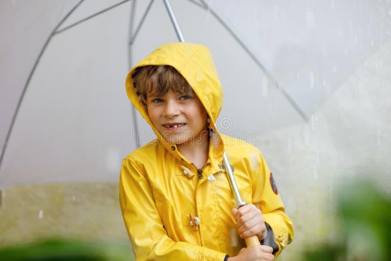 Piękna małe dziecko chłopiec na sposobie szkolny odprowadzenie podczas sleet, ulewnego deszczu i śniegu z parasolem na zimnym dni fotografia stock
