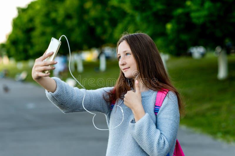 Piękna małej dziewczynki brunetki uczennica Rozmowa na wideo wzywał telefon Sztuki muzyka w hełmofonach Robi gestowi z a zdjęcie stock