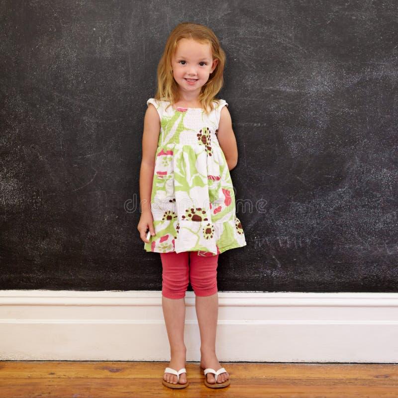 Piękna małej dziewczynki pozycja przeciw blackboard w domu zdjęcie stock