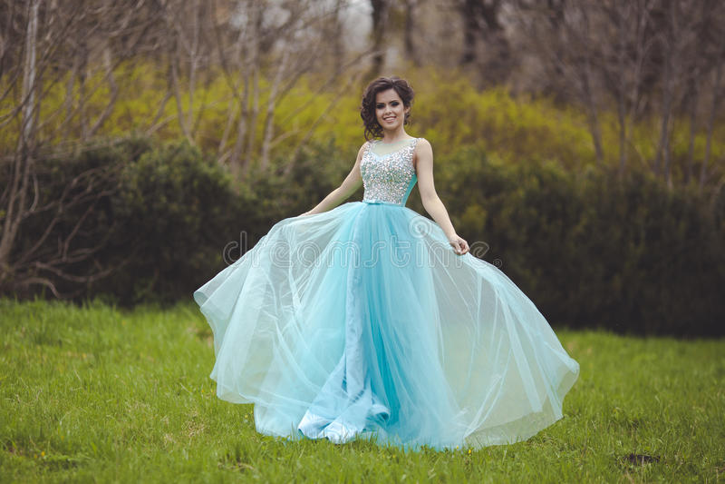 Piękna magisterska dziewczyna wiruje w polanie w błękitnej sukni Elegancka młoda kobieta w pięknej sukni w zdjęcie royalty free