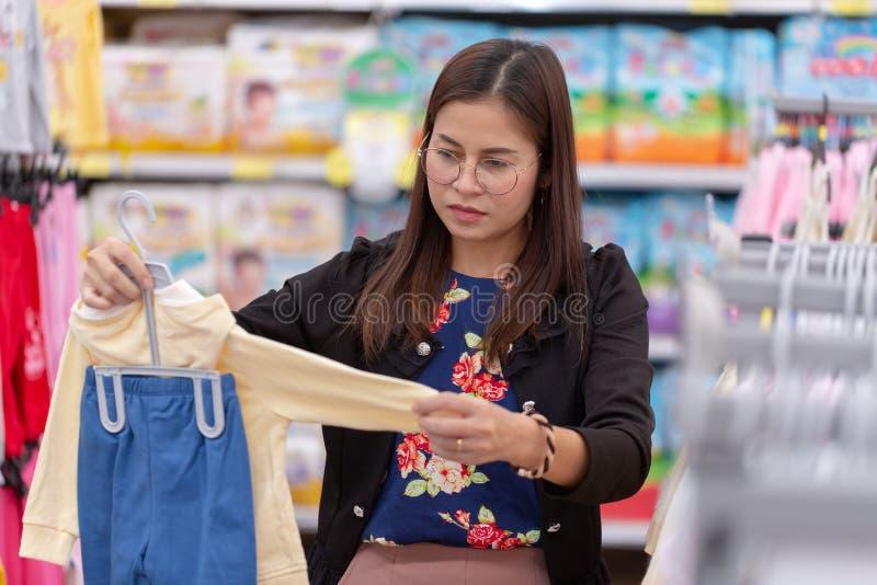 Piękna mama kupuje odziewa dla jej dziecka przy centrum handlowym zdjęcie royalty free