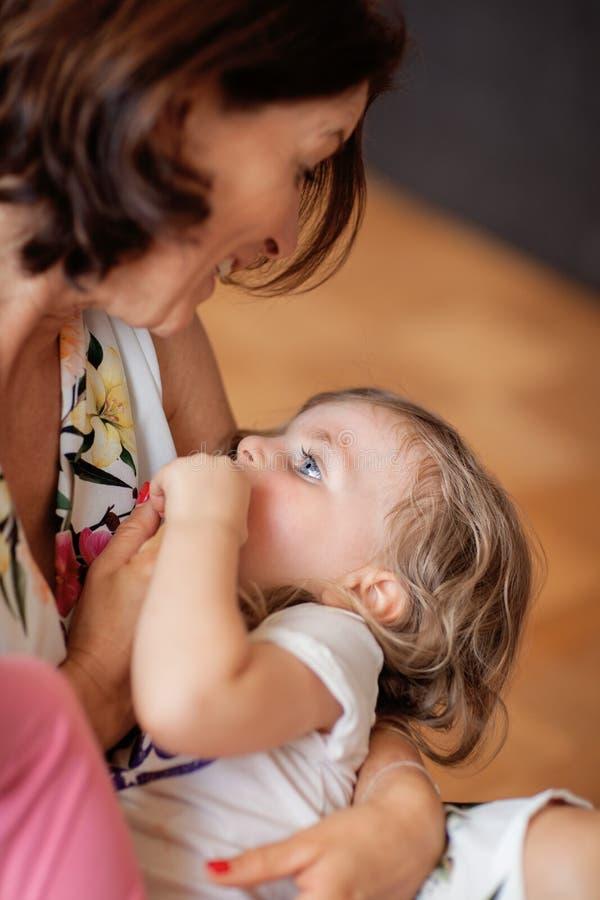 Piękna mama trzyma jej małej córki, opowiada ona obrazy stock