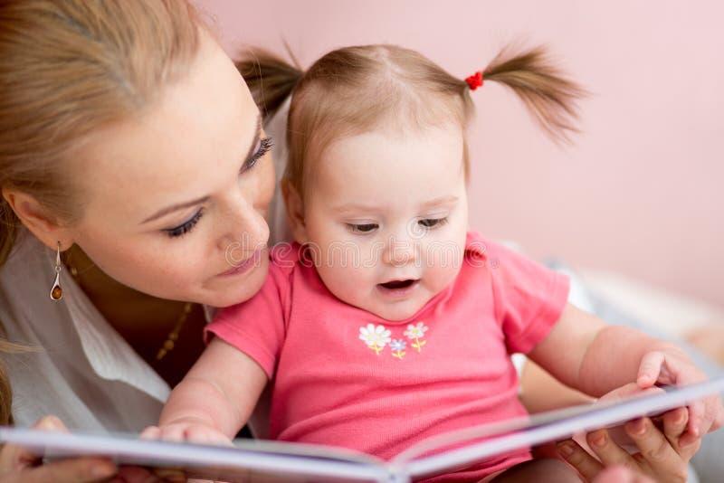 Piękna matka pokazuje wizerunki w książce jej mała dziecko córka w domu fotografia stock