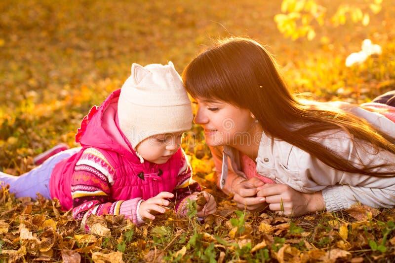 Piękna matki i dzieciaka dziewczyna kłaść na jesiennych liściach outdoors fotografia royalty free
