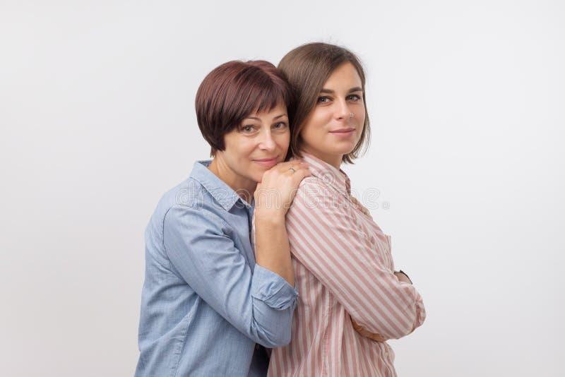 Piękna maturesenior mama i jej dorosła córka ściskamy, patrzejący kamerę i ono uśmiecha się zdjęcie stock