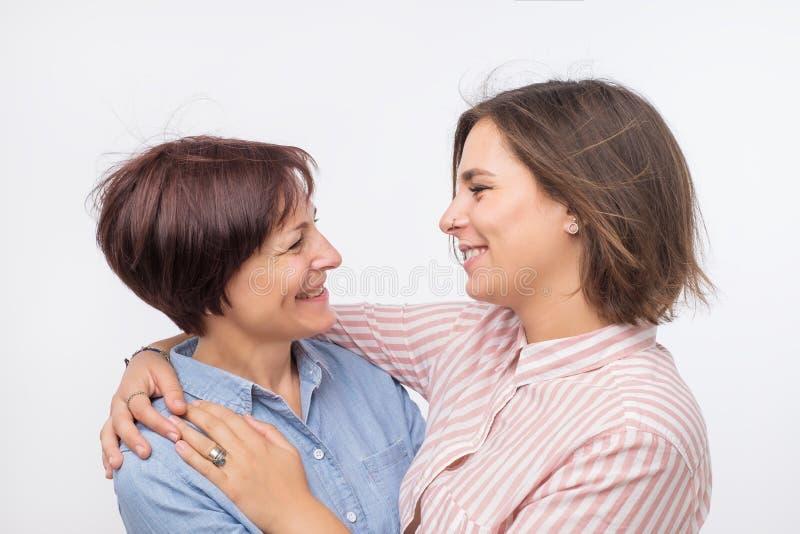 Piękna maturesenior mama i jej dorosła córka ściskamy, patrzejący kamerę i ono uśmiecha się zdjęcia royalty free