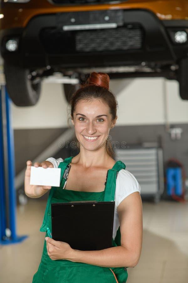 Piękna mechanik dziewczyna pokazuje jej wizytówkę fotografia stock