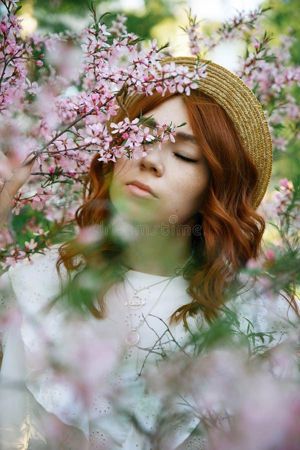 Piękna miedzianowłosa dziewczyna pozuje i marzy w wiosna migdałowych kwiatach fotografia stock