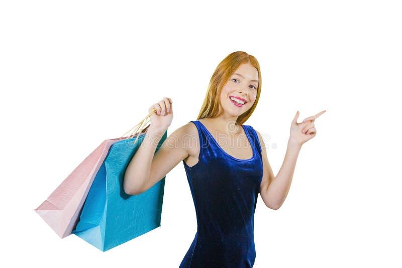 Piękna miedzianowłosa dziewczyna w błękitnej aksamit sukni z torbami nad jej ramieniem pokazuje z jej palcem wskazującym strona zdjęcie stock