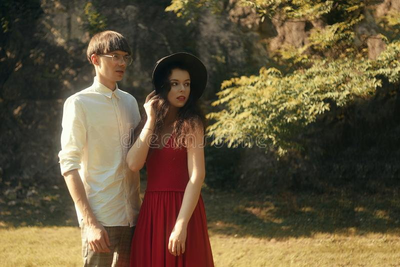 Piękna moda modnisia para w lasowym parku Dziewczyna w pięknym dużym kapeluszu i czerwień tęsk suknia Mężczyzna ubierający fashio fotografia royalty free