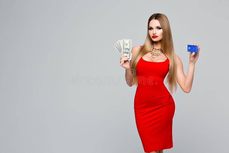 Piękna modna kobieta trzyma kredytową kartę i pieniądze Elegancka nikła kobieta w czerwonej sukni z czerwonymi wargami obraz royalty free