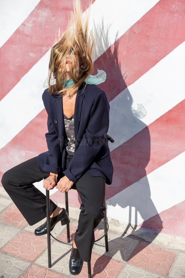Piękna modna młoda kobieta siedzi na krześle blisko pasiastej ściany i trząść jej włosy zdjęcia stock