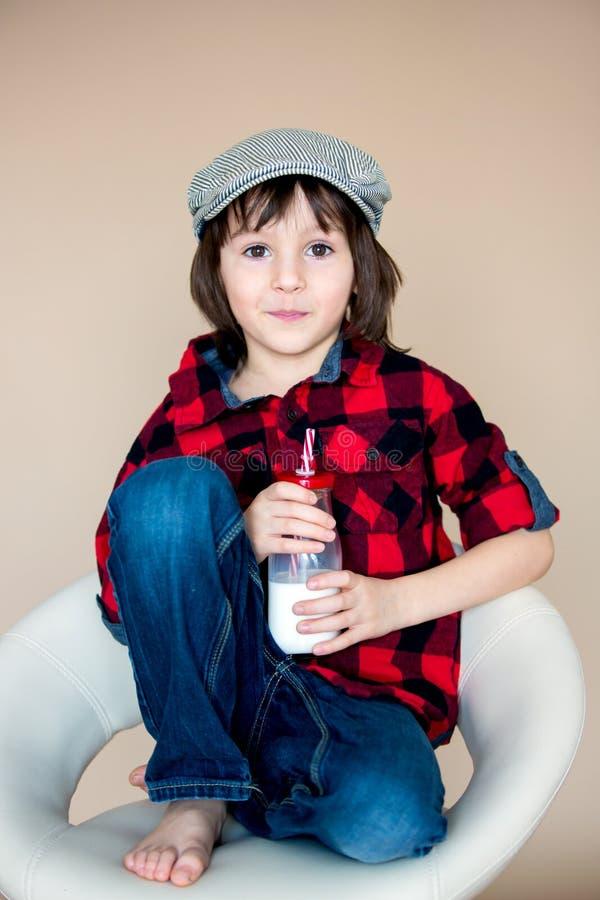 Piękna modna mała preschool chłopiec, pije mleko od b obrazy stock