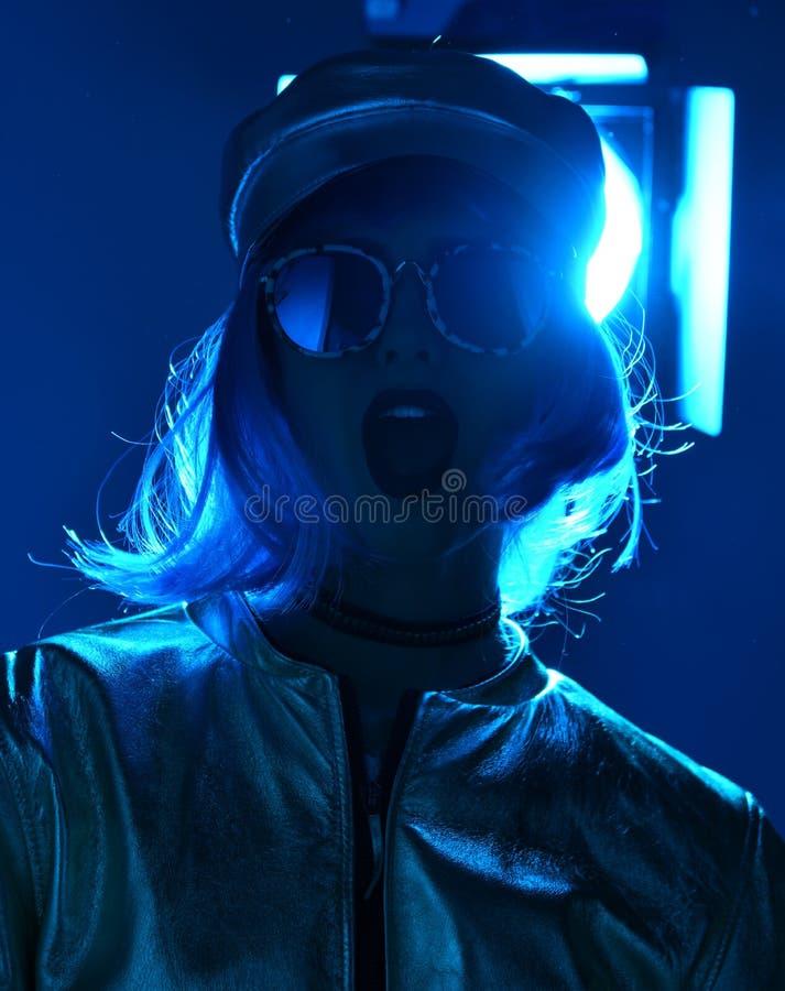 Piękna modniś kobieta jest ubranym wokoło okularów przeciwsłonecznych w błękitnym neonowym świetle w ulica stylu mody jesieni poj zdjęcia royalty free
