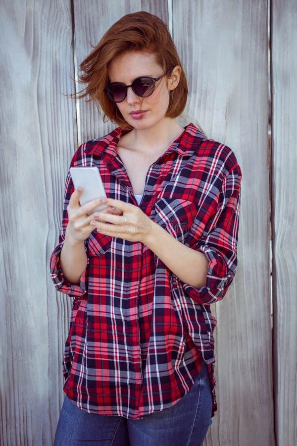 piękna modniś kobieta patrzeje jej telefon komórkowego obrazy royalty free