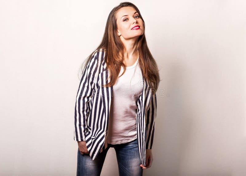 Piękna mody dziewczyna w pasiastej kurtce pozuje na białym bac zdjęcie stock