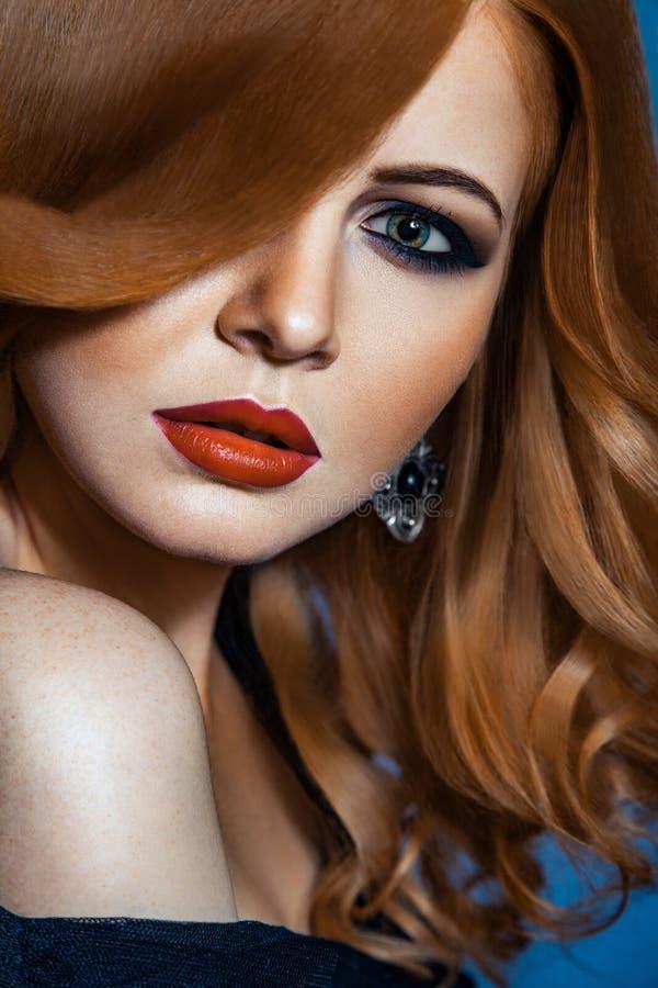 Piękna mody dziewczyna z długim falistym czerwonym brown włosy jasnogłowy model z kędzierzawą fryzurą i modnym dymiącym makeup zdjęcia stock
