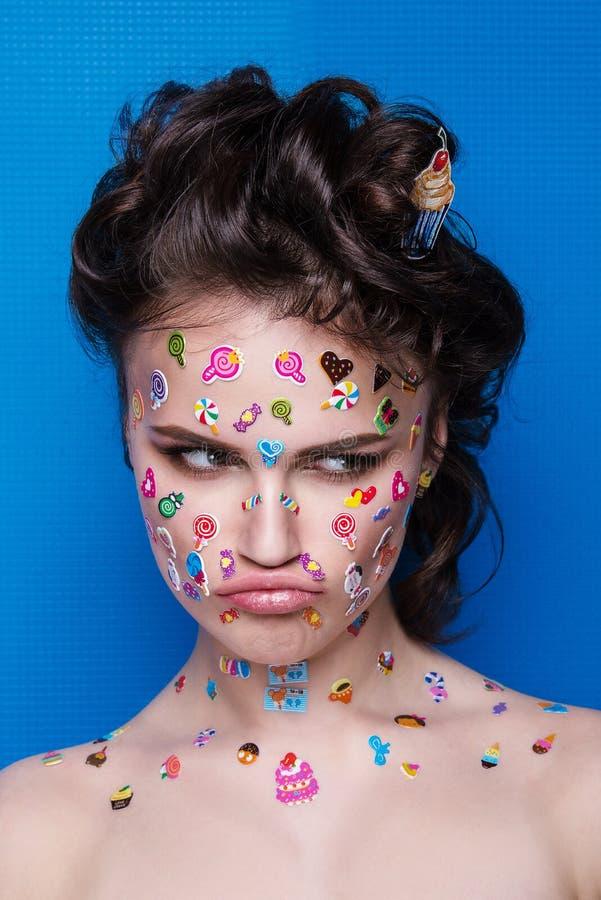 Piękna mody dziewczyna z luksusowym fachowym makeup i śmieszni emoji majchery kleiący na twarzy fotografia stock