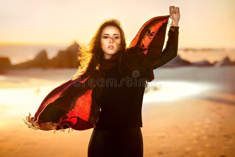 Piękna mody kobieta pozuje na ocean plażowej jest ubranym jesieni odziewa przy zmierzchu czasem fotografia royalty free