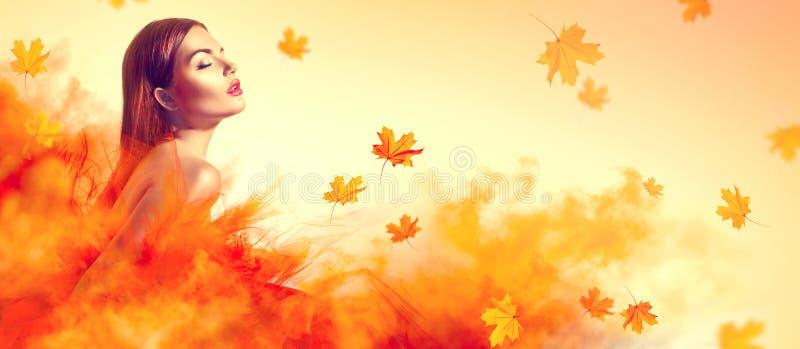 Piękna mody kobieta w jesień koloru żółtego sukni z spadać opuszcza obraz royalty free