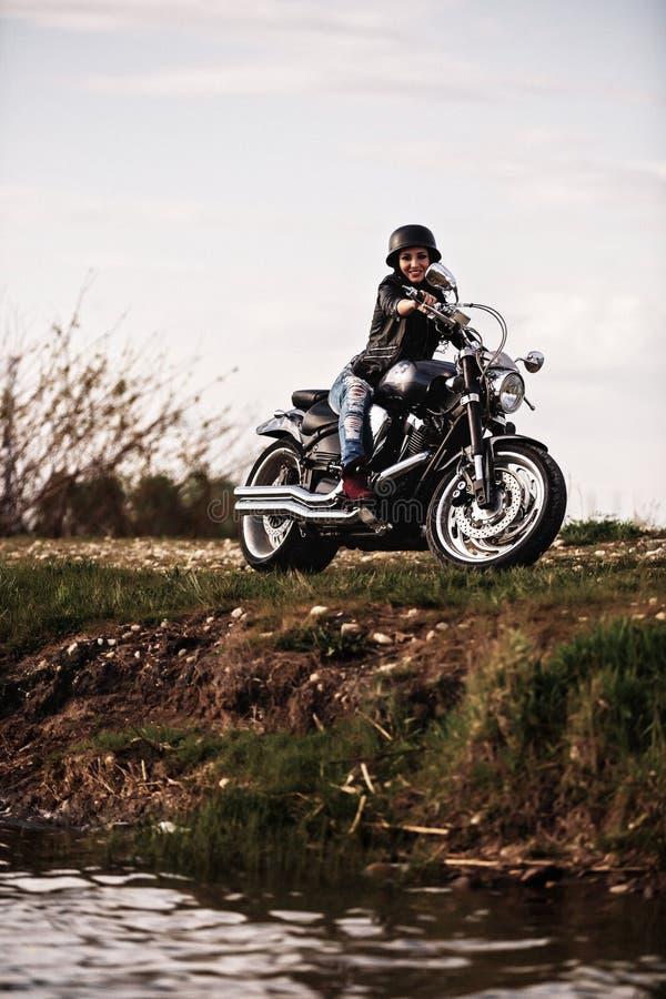 Piękna motocykl brunetki kobieta z klasycznym motocyklem c zdjęcia stock