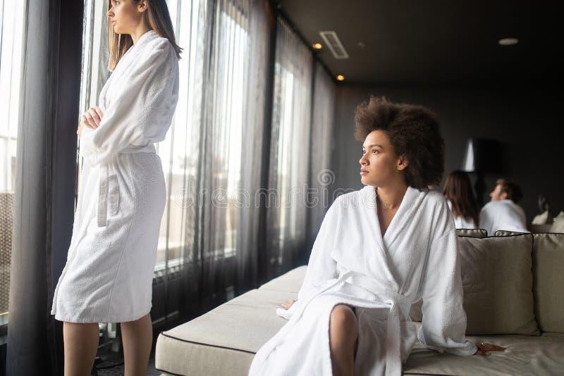 Piękna murzynka relaksuje przy luksusowego hotelu zdrojem jest ubranym bathrobe patrzeje nadokiennego portret obrazy stock