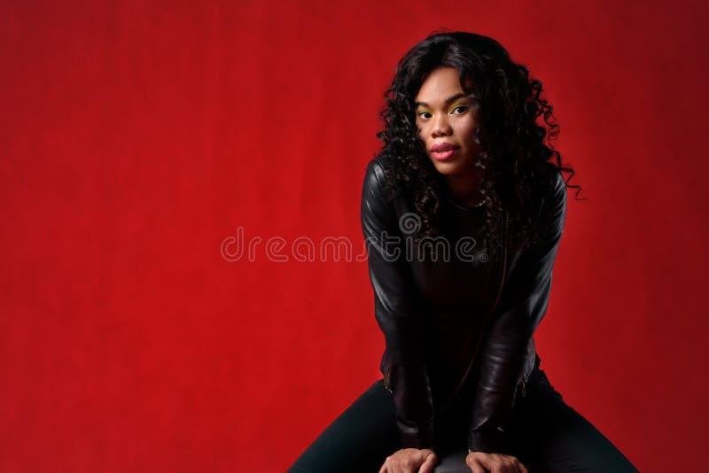 Piękna murzynka w czarnej kurtce na czerwonym tle obrazy stock